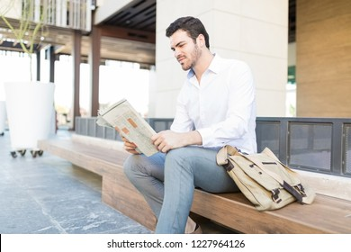 Businessman reading newspaper on bench outside office