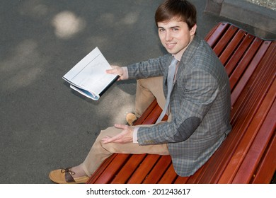 Businessman reading a newspaper on a bench, view from the top