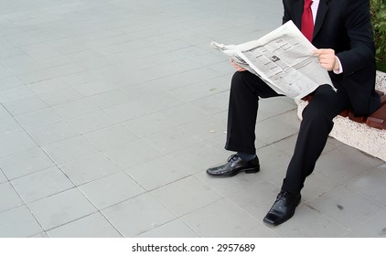 Businessman reading newspaper on the bench