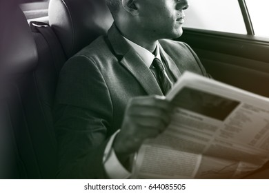 Businessman reading newspaper on the car