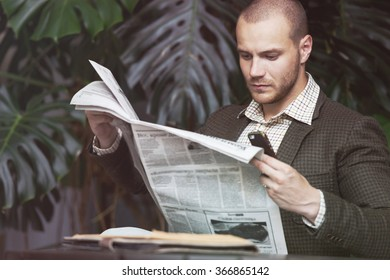 Businessman reading newspaper on chair at office building hall or cafe