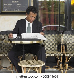 Businessman reading newspaper at outdoor cafe
