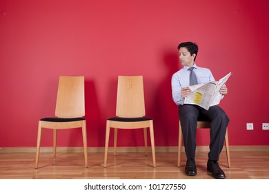 businessman reading the newspaper siting on a chair