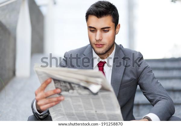 Businessman reading a newspaper in an urban environment