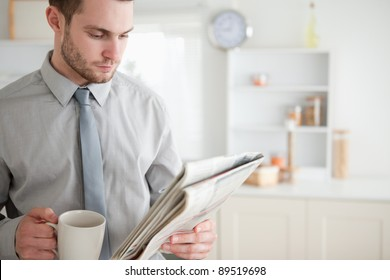 Businessman reading a newspaper while drinking tea in his kitchen