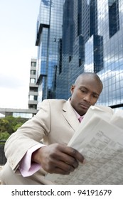Businessman reading the newspaper while sitting down by a modern glass building in the city.