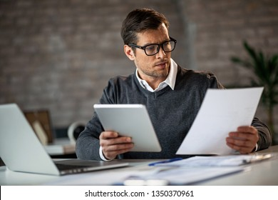 Businessman reading reports and using touchpad while working in the office.