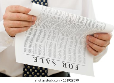 Businessman reading sales ads - closeup on hands and fake text paper