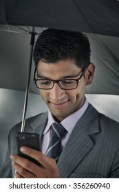 Businessman reading sms on mobile phone