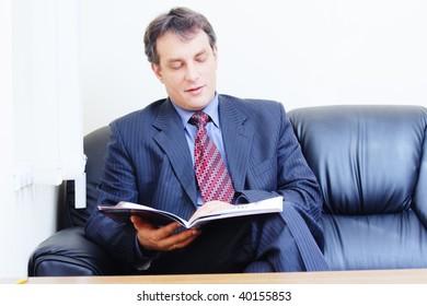 Businessman reads magazine sitting on leather sofa