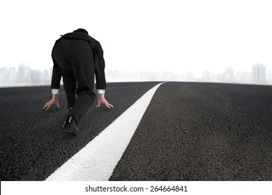 Businessman ready to run on asphalt road with white line and urban scene background