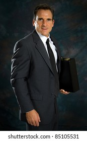 Businessman is ready for work and holds his briefcase under his arm and smiles.