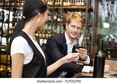 Businessman receive Wine from Waiter with Happy Emotion in restaurant, People Working at restaurant Concept.