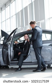 businessman receives from the Manager the keys,sitting behind the wheel of a new car.
