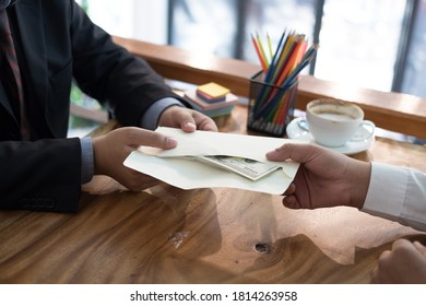 Businessman receiving envelope with money banknote. hand giving cash banknote to man - bribery, corruption, venality concept