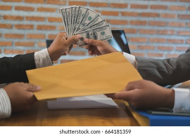 Businessman receiving envelope with money. A man giving contract and cash (banknote) to business people - bribery, corruption, venality concept