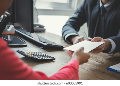 Businessman receiving money in the envelope from a woman at working desk - bribery concept