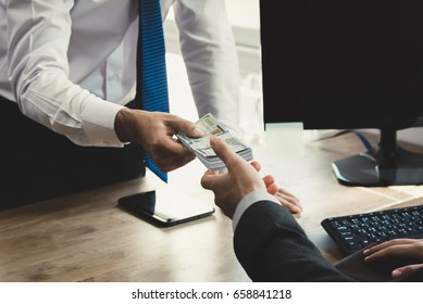 Businessman receiving money from his partner at working desk in the office - loan, bribery and corruption concepts