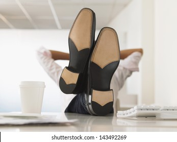 Businessman reclining with his feet up on computer desk in office