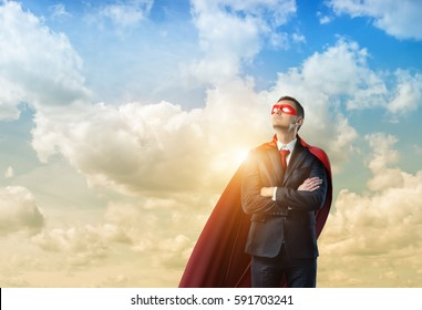 Businessman in a red cape and a red eye mask standing with hands crossed on clouded sky background. Business and success. Corporate hero. Superpowers and coaching.