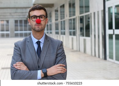Businessman with a red clown nose crossing his arms