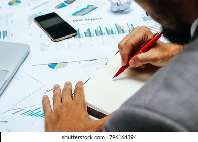 businessman with red pen writing notebook or making notes on office desk table. with laptop and smartphone to analysis business report document for new startup project. business concept.