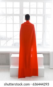 Businessman in red superhero cloak stands with his back to the camera. Young man in suit and superman cape.