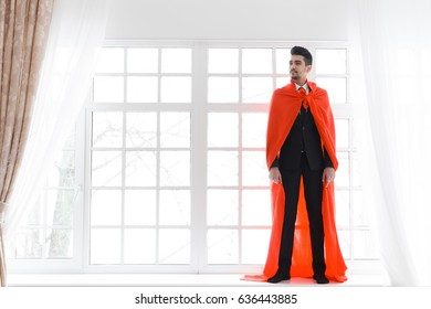 Businessman in red superhero cloak. Young man in suit and superman cape. copyspace
