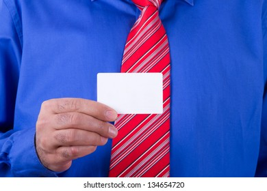Businessman with red tie and blue shirt holding and showing blank, empty, white business card.