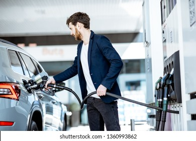 Businessman refueling his luxury car holding filling gun at the gas station