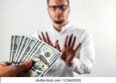 The businessman refuses US dollars in the studio on a gray background. The concept of corruption. One hundred dollar bills. The concept against corruption in business activities, against bribery.