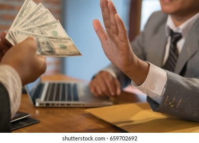 Businessman rejecting money cash banknote from a man.  honest business people in suit refuse to take the bribe - anti bribery, corruption, venality concept.