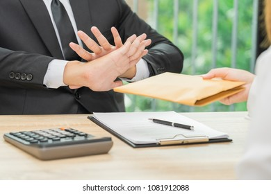 Businessman rejecting money in envelope offered by a woman - corruption concepts.