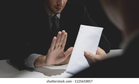 Businessman rejecting money in envelope offered by his partner in shadow for anti bribery and white collar crime concept