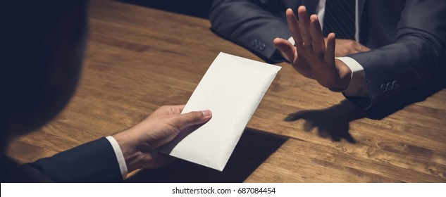 Businessman rejecting money in white envelope offered by his partner in the dark, anti bribery concept - panoramic banner