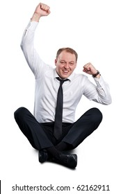 Businessman rejoices as he sits cross-legged on the floor. Isolated on white background.