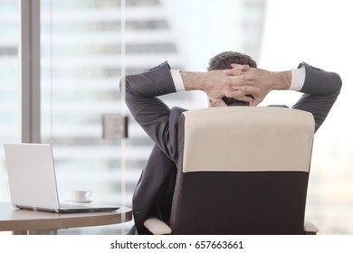 Businessman relaxes sitting in the office and looking in window