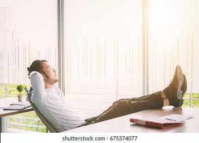 Businessman relaxing concept: businessman sitting with feet up at office desk