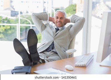 Businessman relaxing at desk and smiling at camera in his office