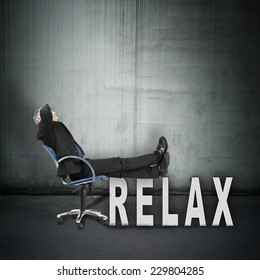 Businessman relaxing in office chair, concept of success and rest