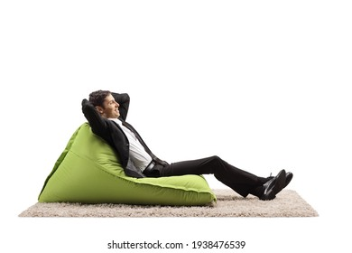 Businessman relaxing on a green bean bag chair isolated on white background