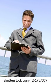 Businessman relaxing outdoors with tablet