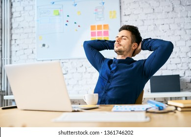 Businessman relaxing at work with hands behind head, eyes closed and coffee