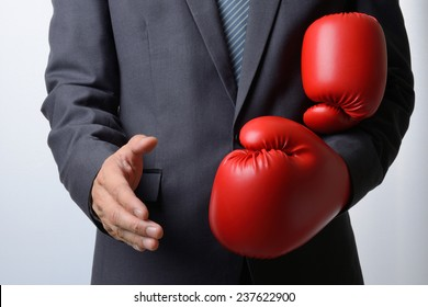 Businessman remove red boxing gloves to offer a handshake on white background,compromise concept