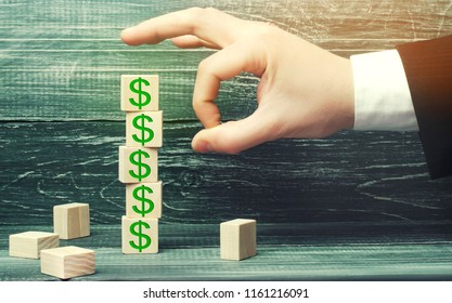 businessman removes a cube with a picture of dollars. financial and economic crisis. capital outflow. sabotage of the economy. bankruptcy. pressure on small businesses. falling prices. cash loss