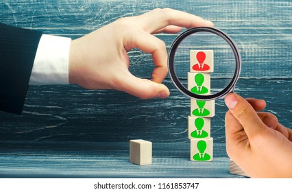 the businessman removes / dismisses the employee from the team. management within the team. wooden blocks with a picture of workers. control arm. leader
