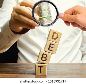 Businessman removes wooden blocks with the word Debt. Debt relief or cancellation is the partial or total forgiveness of debts, or the slowing or stopping growth. Restructuring. Pay. Selective focus