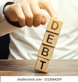 Businessman removes wooden blocks with the word Debt. Debt relief or cancellation is the partial or total forgiveness of debts, or the slowing or stopping growth. Restructuring. Pay. Redemption