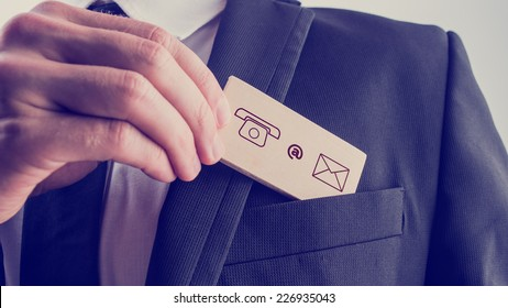 Businessman removing a wooden card with contact icons from the pocket of his suit jacket, vintage effect toned image.