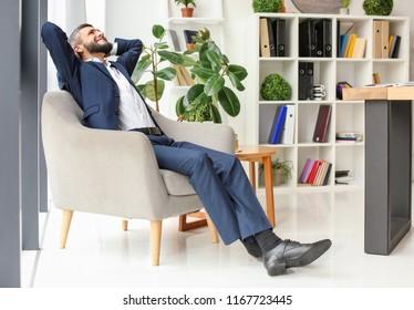 Businessman resting in armchair indoors